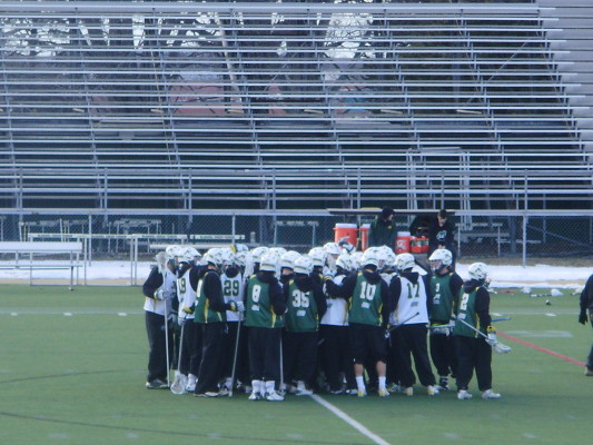 The men's lacrosse team huddles up. Photo by Elec Trainor