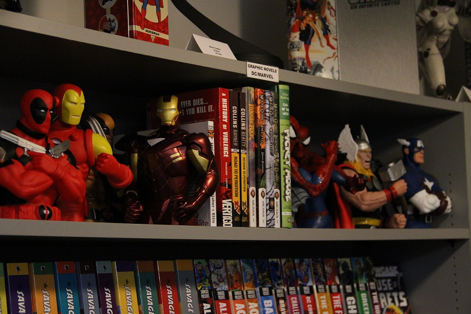 Several figurines of familiar comic book characters sit atop a shelf.