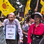 An elderly couple marching and showing their endurance and will to change the planet.