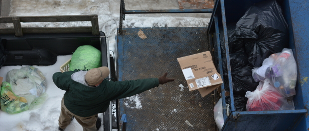 A physical plant employee tosses recyclable cardboard in the garbage. Photo by Kyle Parks