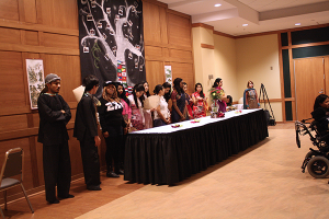 The models and performers for the finale of the event, the fashion show, gather while the club's advisor, Dr. Lemke, gives the concluding speech. They wear traditional dress and props brought from Asia by members and even a member's family.