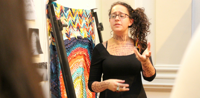"Senior Mangie Moreno Mora showcases her performance art during this year's art honors exhibition, ""Honorable Discharge."""