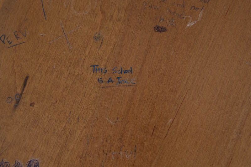 A student expresses their discontent with McDaniel, via pen carvings on a desk in Lewis.