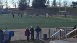 Bundled-up parents look on as McDaniel attempts to defend a St. Mary's (Md.) attack on goal.
