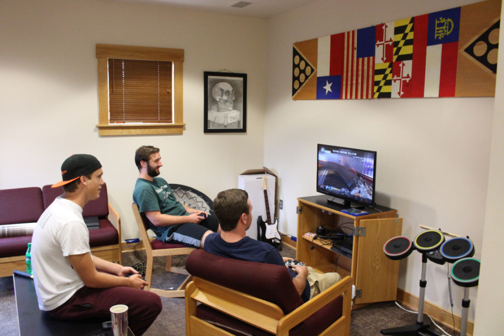 Suite mates Aaron Lutz, Morgan Shugars, and Bryan Fidler enjoy playing games in their decorated common room.