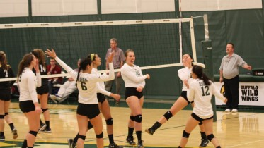 The Green Terror celebrate a point during their 3-0 sweep of Ursinus on Saturday. Photo by Atticus Rice.