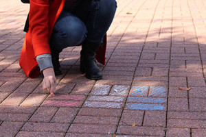 A McDaniel student drawing the French flag on Red Square during French Week